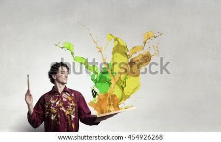Man artist painting with brush . Mixed media - stock photo