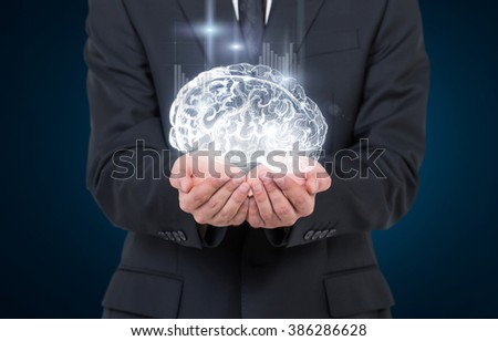 Man as if holding shining image of brain in hands, graphs from it. Breast view. Concept of mental activity.