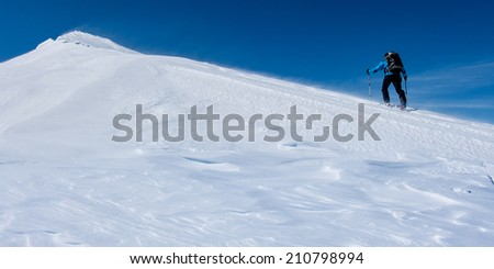 Man ascending a snow covered mountain slope - stock photo