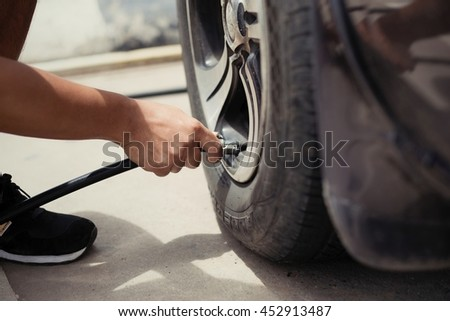 Man asia driver checking air pressure and filling air in the tires of car