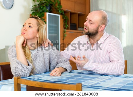 Man asking for forgiveness from sad woman at home - stock photo