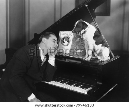 Man asleep at piano with dog - stock photo