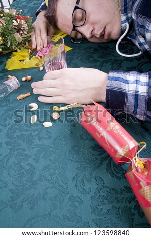 man asleep holding glass with head on table after christmas party - stock photo
