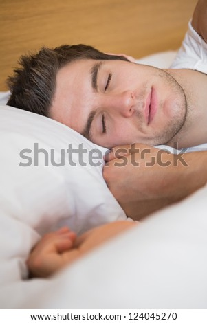 Man asleep in bed in hotel room - stock photo