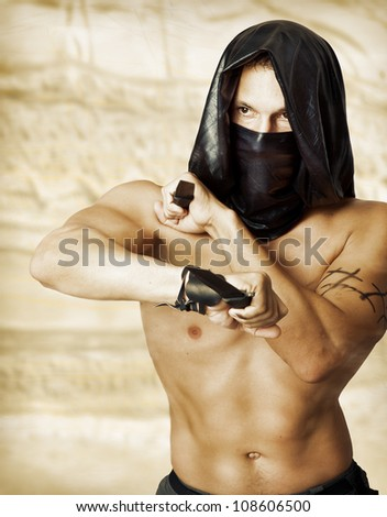 Man assassin with sexy torso in black mask and hood holding two knifes in hands - stock photo