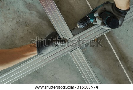 Man assembles profile metal frame for plasterboard ceilings