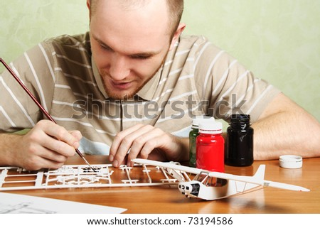 man assembling plastic airplane model and painting pieces - stock photo