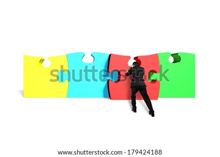 Man assembling puzzles in white background - stock photo