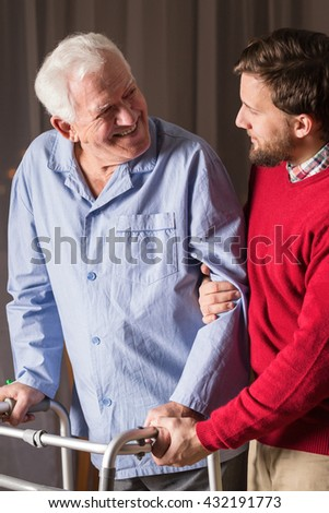 Man assisting senior man with walking zimmer.