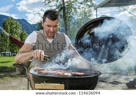 Man at a barbecue grill with smoke