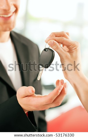 Man at a car dealership buying an auto, the female sales rep giving him the key, macro shot with focus on hands and key - stock photo