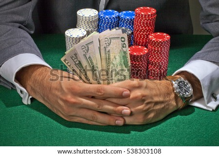 Man at a poker table betting on his hand