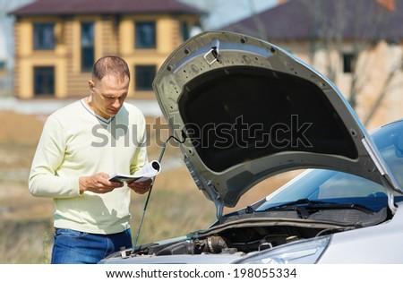 man at  broken car reads user guide - stock photo