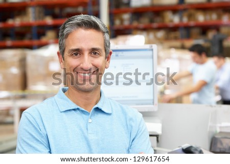 Man At Computer Terminal In Distribution Warehouse - stock photo