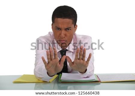 Man at desk making stop gesture - stock photo