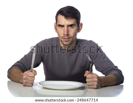 Man at dinner table with fork and knife raised. Hunger strike isolated over white background  - stock photo