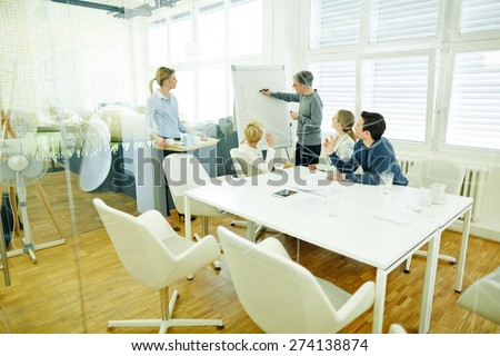 Man at flipchart in business meeting in a conference room - stock photo