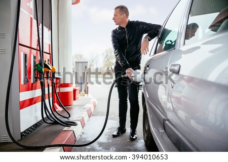 Man At Gas Station Filling Up Her Car With Petrol