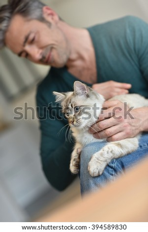Man at home cuddling beautiful cat