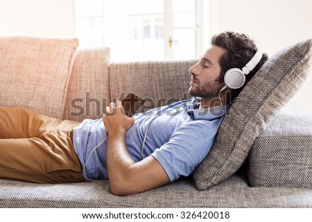 Man at home on sofa listening a music with a smartphone - stock photo
