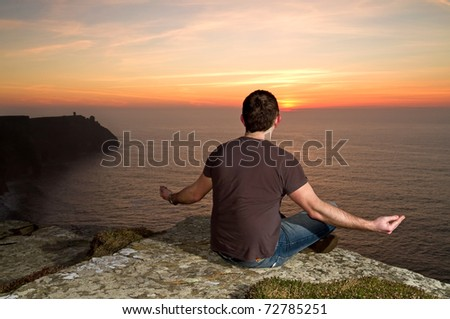 Man at meditation on Cliffs of Moher at sunset - stock photo