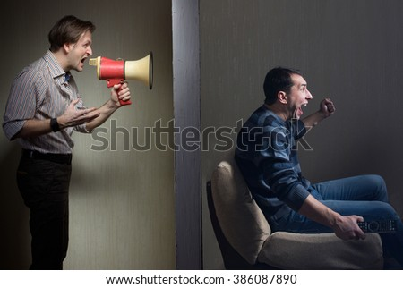 Man at night yells through a megaphone at the noisy neighbor - stock photo