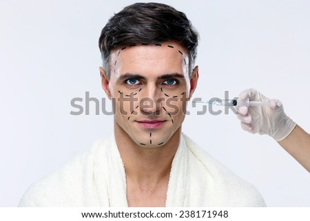 Man at plastic surgery with syringe in his face - stock photo