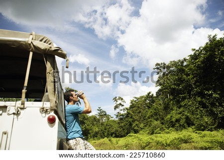 Man at SUV Filming with Camcorder - stock photo