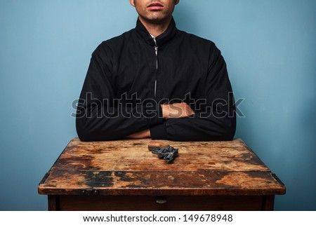 Man at table with gun - stock photo