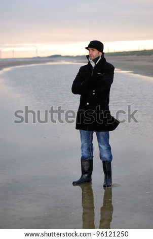man at the beach while sun rising - stock photo
