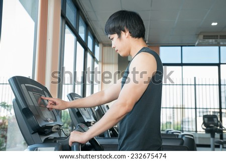 Man at the gym doing set up treadmill for fitness - stock photo