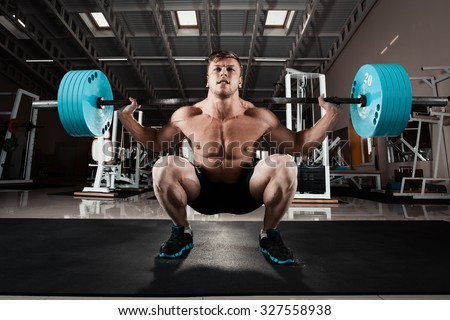 Man at the gym. Execute exercise squatting with weight, in gym - stock photo