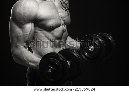 Man at the gym. Man makes exercises dumbbells. Sport, power, dumbbells, tension, exercise - the concept of a healthy lifestyle. Article about fitness and sports. - stock photo