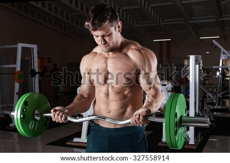 Man at the gym. Man makes exercises with barbell - stock photo
