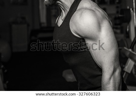 Man at the gym. Man makes exercises with barbell. Sport, power, dumbbells, tension, exercise - the concept of a healthy lifestyle. Article about fitness and sports.