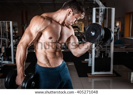 Man at the gym. Man makes exercises with dumbbells
