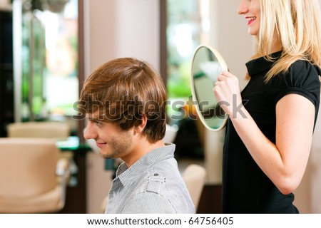 Man at the hairdresser, she has finished the cut and is showing the result in the mirror