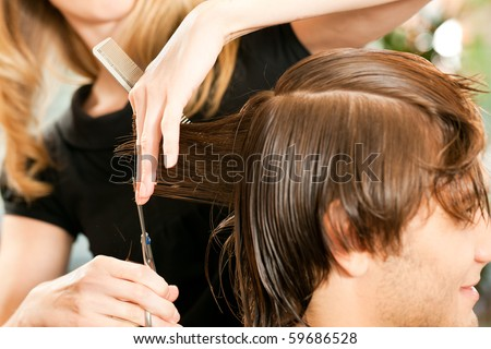 Man at the hairdresser, she is cutting - close-up with selective focus on her hand - stock photo