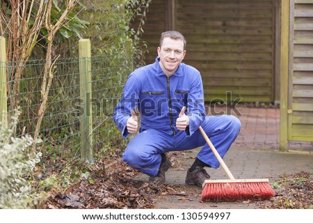 man at work.   groundskeeper (caretaker service) cleaning a garden path.  positive expression with thumb up.