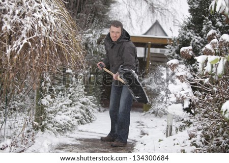 man at work. groundskeeper (caretaker service) removing snow with a shovel. - stock photo