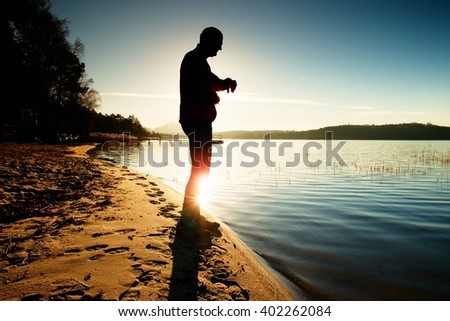 Man athlete checking time during workout run exercise outdoors at ocean beach in sunny cold morning. Runner in pink sportswear. - stock photo