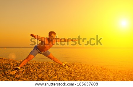 man athlete practicing, playing sports and yoga on the beach at sunset - stock photo