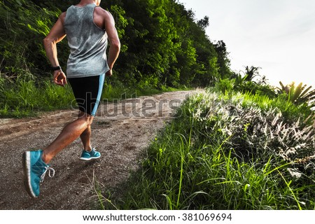 Man athlete running on the gravel road with green grass and trees on its sides - stock photo