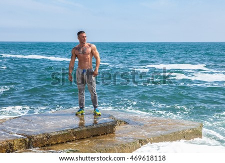 Man Athlete stands on a rock by the sea
