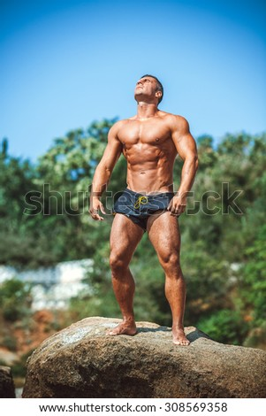 Man Athlete stands on a rock by the sea against the sky - stock photo
