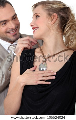 Man attaching his wife's necklace - stock photo