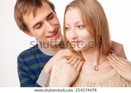 Man attaching necklace to girl's neck. man standing behind woman . Isolated over white background. - stock photo
