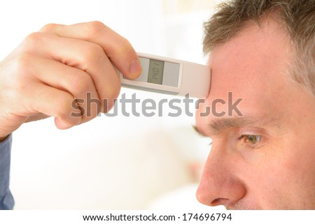 Man attempting to measure body temperature with thermometer on forehead - stock photo