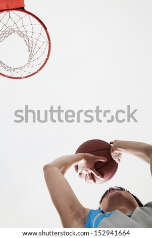 Man attempting to through basketball in to the basket - stock photo