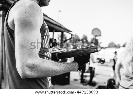 Man attends body pump workout. Doing biceps exercises to get strong hands. Lifting weights.